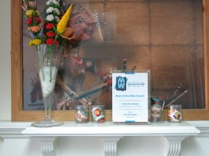 The Social Media Best of the Web Award won by the Collections People Stories review team on the mantelpiece at the SCC