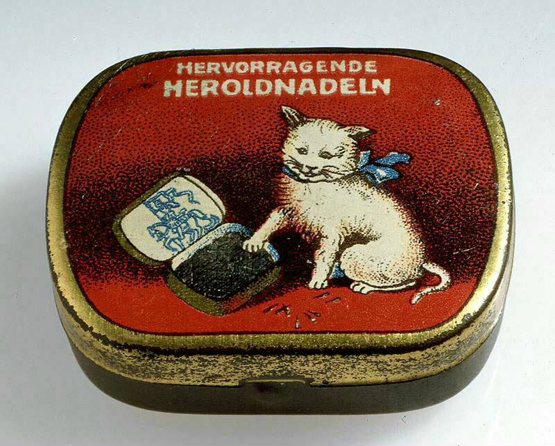A tin for gramophne needles, decorated with a picture of a cat playing with the needles