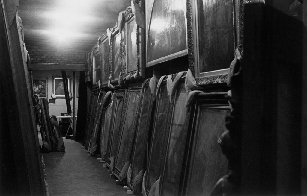 National Gallery paintings in storage in the Manod caves, hanging in two rows on racks, with padding wrapped around their corners. Photo: © The National Gallery London.