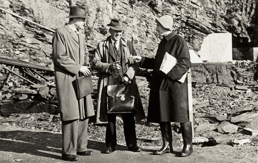 Three men - from left to right, Ian Rawlins of the National Gallery, Mr Vaughan the quarry manager, and Martin Davies of the National Gallery, standing talking outside the entrance to Manod Quarry, Wales.